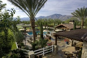 View from atop the sky deck to the main home/pool house & mountains beyond at this La Quinta estate.